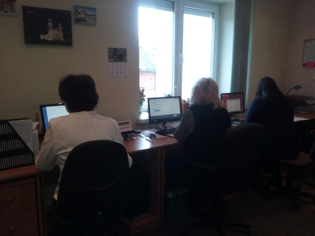 Darbuotojos tikrina kompiuteriuose pranešimus iš policijos.